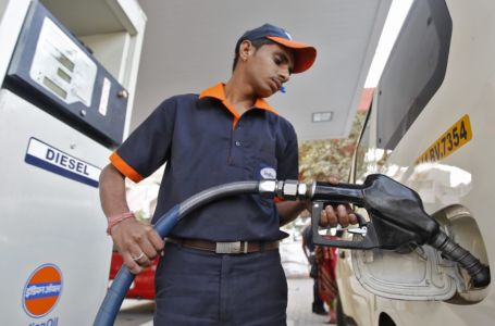 Worker fills diesel in a vehicle at a fuel station in Ahmedabad